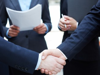 Close-up of businessmen handshaking in working environment
